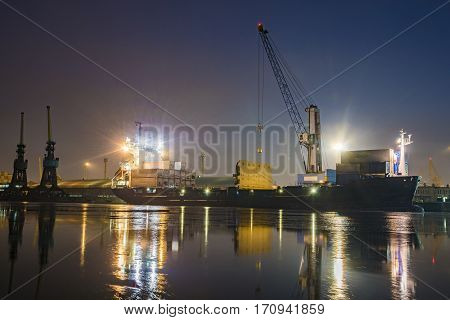 unloading cargo ship with containers in sea port at night