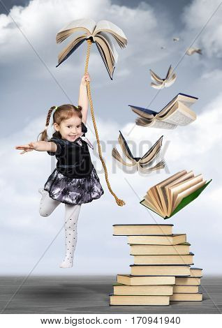 Education concept child girl fly on book