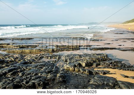 Rocks on sea shore against ocean and blue skyline in South Africa