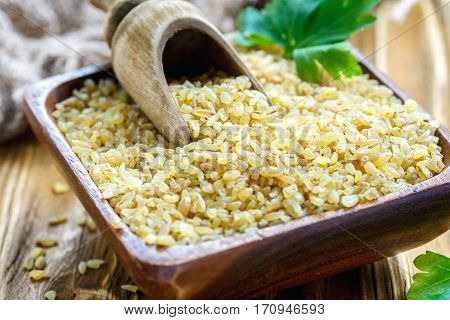 Wooden Scoop In A Bowl With Bulgur.