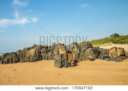 Rocks On Sandy Beach And Blue Coastal Skyline