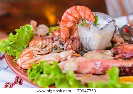 A huge plate of seafood. Very tasty food on a light background.