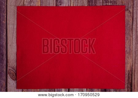 Red fleece background on wood. Flat lay top view.