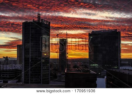 Skyscrapers with dramatic colorfull sunset. Prague business center. Modern urban style. Construction of skyscraper.