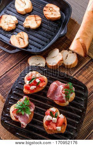Set Of Crostini With Tomato, Arugula, Prosciutto And Mozzarella. Italian Food, Homemade Bruschetta.