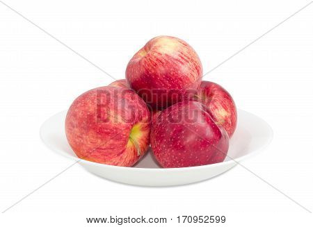 Several red ripe apples on a white dish on a light background closeup