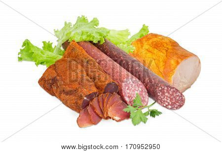 Partly sliced two pieces of the dried pork tenderloin two varieties of dry smoked sausage and ham with turkeys with parsley twig and lettuce on a light background