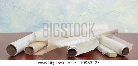 Several rolls of the plastic oven bags plastic food wrap aluminum foil and various parchment paper for household use closeup on a dark red wooden table