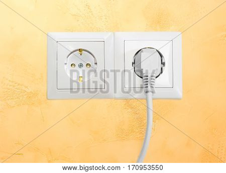 Block of the two white socket outlets European standard with connected one white power cable with corresponding AC power plug closeup on a yellow wall
