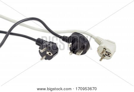 Black AC power plug of United Kingdom standard and one black and one white power plugs of combined German and French standard with fragment of a power cords on a light background
