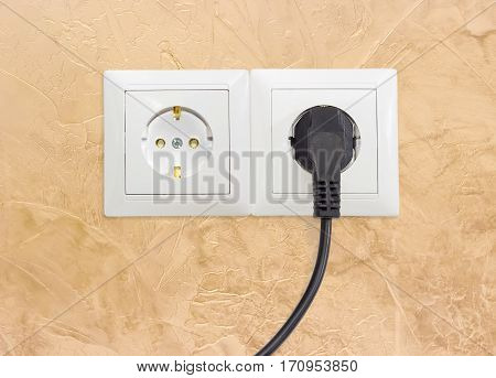 Block of the two white socket outlets European standard with connected one black power cable with corresponding AC power plug closeup on a yellow wall