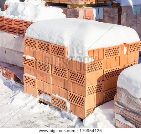 Red perforated bricks with round holes covered snow on a pallet against the background of other pallets with bricks on an outdoor warehouse in winter sunny day