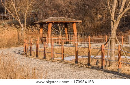 Korean style gazebo in a woodland park next to a gravel walkway