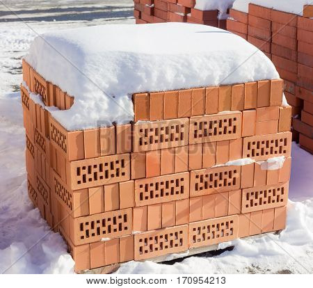Red perforated bricks with rectangular holes covered snow on a pallet on an outdoor warehouse in winter sunny day