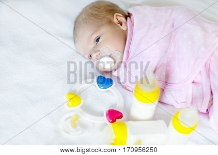Cute newborn baby girl with nursing bottles, rattle and pacifier. Formula drink for babies. New born child, little girl laying in bed. Family, new life, childhood, beginning, bottle-feeding concept.