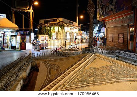HERSONISSOS, CRETE - SEPTEMBER 18, 2016 - View of the Roman Sarakino fountain along the waterfront at night with tourist shops to the rear Hersonissos Crete Greece Europe, September 18, 2016.