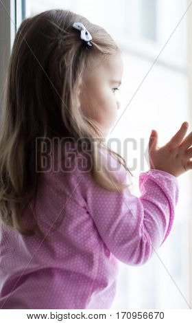 Cute little girl standing on the windowsill near the window