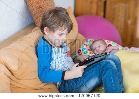 Preschool kid boy playing games tablet computer during babysitting. Cute newborn baby looking on brother. Adorable kids and children at home.