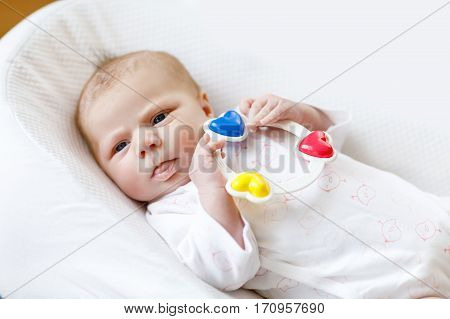 Cute adorable newborn baby playing with colorful rattle toy. in white bed at home. New born child, little girl looking surprised at the camera. Family, new life, childhood, beginning concept
