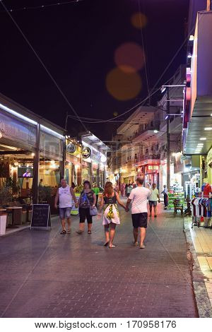 HERSONISSOS, CRETE - SEPTEMBER 18, 2016 - Waterfront restaurants and bars along a harbour shopping street at night Hersonissos Crete Greece Europe, September 18, 2016.