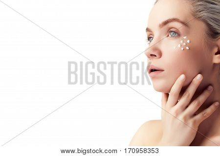 Beautiful Woman With Cream Drops On Face On White Background