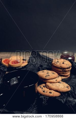 Cup Of Tea With Chocolate Cookies And Biscuits On Black Table Background. Afternoon Break Time. Brea