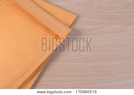 Used Yellow Blank Envelope With Transparent Bubble Wrap Or Packaging Shockproof On Wooden Table.