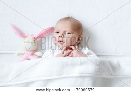 Cute adorable newborn baby playing with pink plush animal rattle toy. in white bed at home. New born child, little girl looking surprised at the camera. Family, new life, childhood, beginning concept