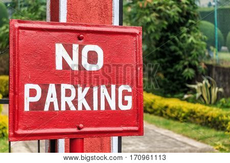 Red retro sign prohibiting parking before restricted area