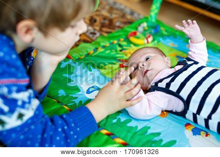 Happy little kid boy with newborn baby girl, cute sister. Siblings. Brother and baby playing with colorful toys and rattles together. Kids bonding. Family of two bonding, love.