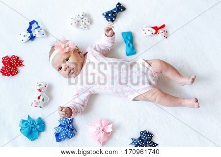 Cute adorable newborn baby with colorful bows. New born child, little girl looking surprised at the camera. Family, new life, childhood, beginning concept.