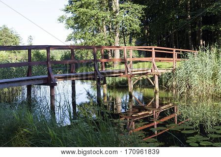 photographed close-up details of an old wooden bridge over a small river. Summer season.