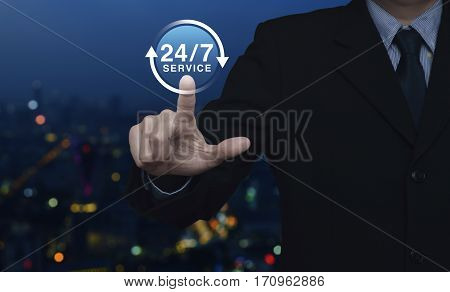 Businessman pressing button 24 hours service icon over blur colorful night light city tower Full time service concept