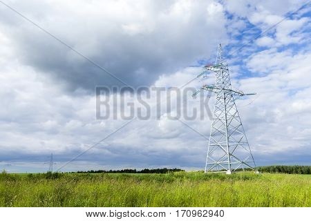 metal poles for electrical lines in the field. Photo close-up in summer. Focus on the pole. In the background the sky with clouds