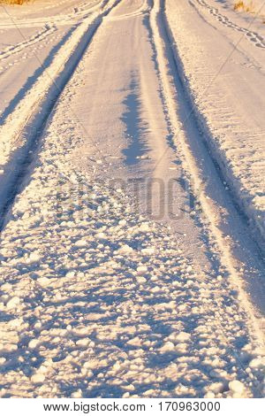 snow remaining on the track after a passing car. Photo close-up from top to bottom. Small depth of field. Winter season