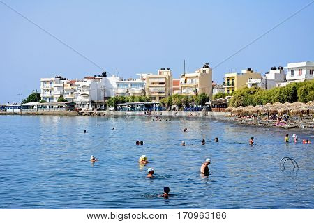IERAPETRA, CRETE - SEPTEMBER 18, 2016 - Tourists relaxing on the beach with buildings to the rear Ierapetra Crete Greece Europe, September 18, 2016.