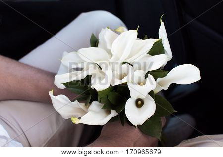 Fiance holding a wedding bouquet of white callas flowers