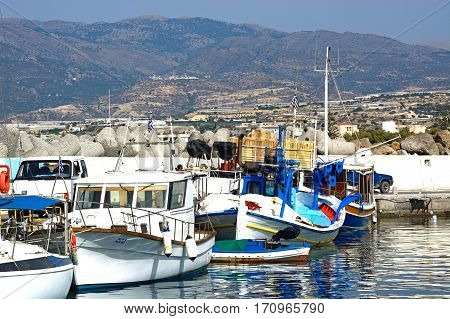 IERAPETRA, CRETE - SEPTEMBER 18, 2016 - Fishing boats moored in the harbour with views towards the mountains Ierapetra Crete Greece Europe.