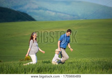 Beautiful young family, father and pregnant mother with little son on a walk against green fields and hills.