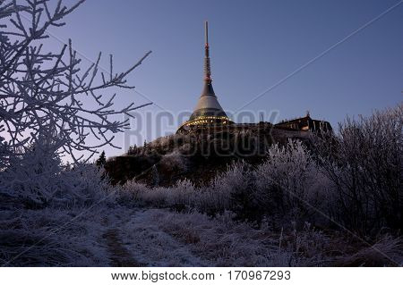 The evening view on Jested in Liberec in Czech republic.  The tower on hill and rock. Clear dark blue sky. The modern building. Winter time. Frozen trees before the Jested in winter.