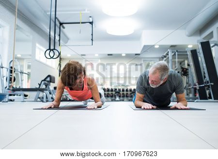 Beautiful fit senior couple in gym in plank position working out abs