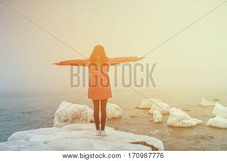 beautiful smiling with arms outstretched on the beach
