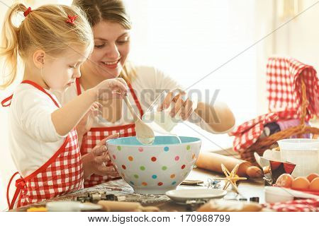 Mum and daughter baking cakes early in the morning.