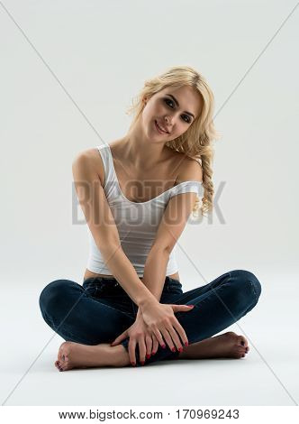 Young beautiful woman in sexy white top and jeans sitting on the floor in studio posing with a smile