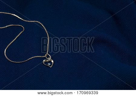 One golden chain with pendant in form of heart on the deep blue background