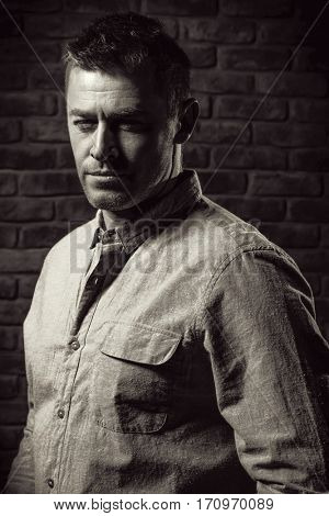 Black-and-white portrait of a handsome mature man standing by the brick wall. Men's beauty, fashion.