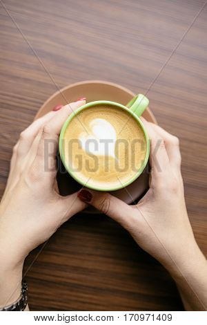 Cup of coffee latte with a heart symbol. Woman's hands holding cup of caffe latte in a cafe