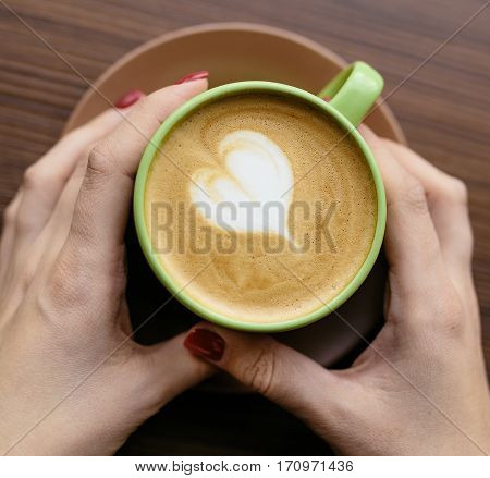 Cup of coffee latte with a heart symbol. Woman's hands holding cup of caffe latte in a cafe. close up