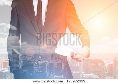 Creative image of young man with helmet on abstract city background. Workers security concept. Double exposure