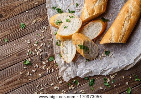 Photo of baguette with herbs on table with seeds